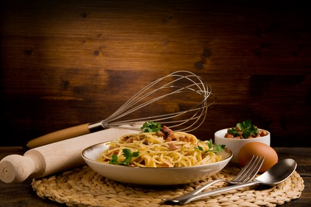 carbonara: Delicious spaghetti with bacon and egg called alla carbonara on wooden table