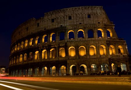 photo of the roman colosseum taken by night with dark blue sky photo