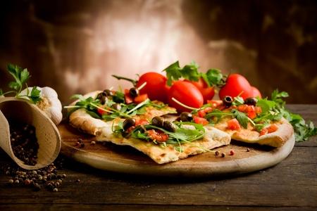 comida italiana: foto de la pizza vegetariana deliciosa con r�cula en la mesa de madera
