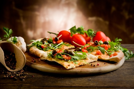 vegetarian cuisine: photo of delicious vegetarian pizza with arugula on wooden table