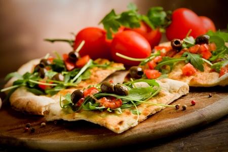 panadero: foto de la pizza vegetariana deliciosa con rúcula en la mesa de madera