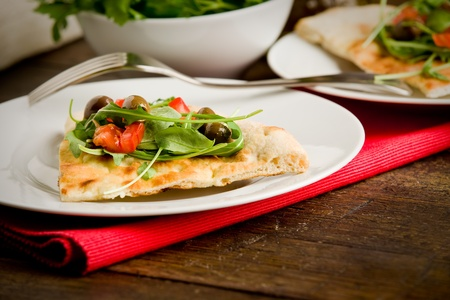 photo of delicious vegetarian pizza with arugula on wooden table photo
