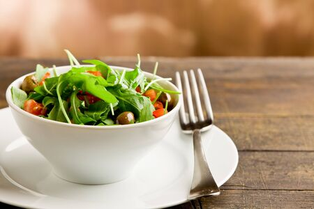 photo of deliciuos light salad with arugula and tomatoes in white bowl on wooden table photo