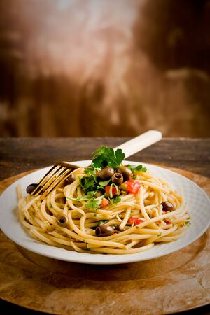 italian pasta: delicious vegetarian dish of pasta with olives and parsles on wooden table
