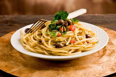 delicious vegetarian dish of pasta with olives and parsles on wooden table