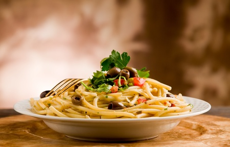delicious vegetarian dish of pasta with olives and parsles on wooden table photo