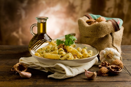 italian cuisine: Italian regional dish made of pasta with walnut pesto on wooden table