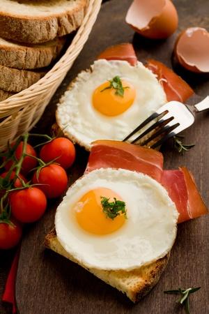 huevos fritos: foto conceptual de desayuno Inglés con huevos fritos y tocino en la mesa de madera