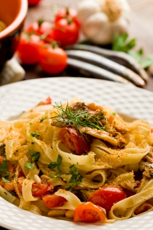 mediterranean cuisine: Italian regional dish made of pasta with sardines on wooden table Stock Photo