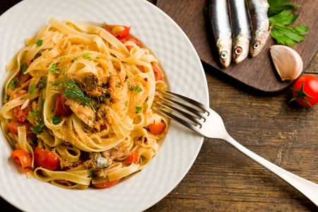 sardines: Italian regional dish made of pasta with sardines on wooden table Stock Photo
