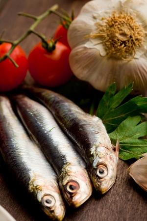 sardinas: foto de sardinas e ingredientes diferentes listos para ser procesados ??en la mesa de madera