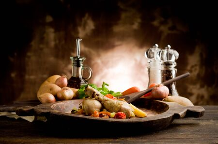 rustical: delicious stewed chicken with vegetables inside rustical wooden plate Stock Photo