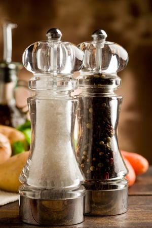 Foto von Salz-und Pfeffermühle mit Zutaten arround auf Holztisch