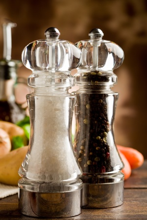 black pepper: photo of salt and pepper mill with ingredients arround on wooden table
