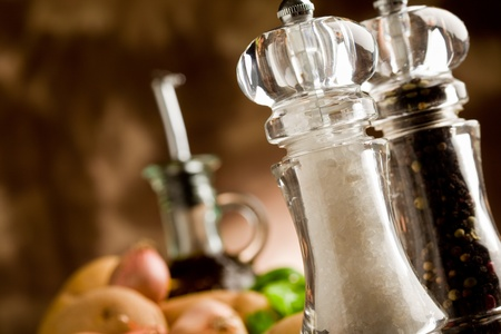 photo of salt and pepper mill with ingredients arround on wooden table photo