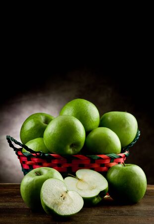 photo of delicious green apple inside a basket on wooden table Stock Photo - 11812916