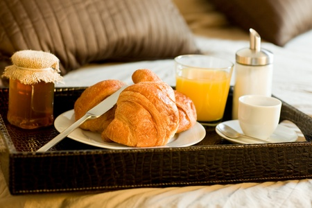 photo of tray with breakfast food on the bed inside a bedroom photo