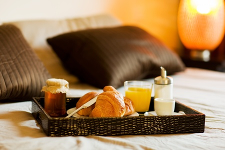 luxury hotel room: photo of tray with breakfast food on the bed inside a bedroom