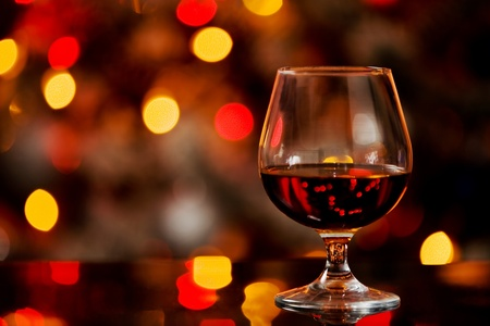 photo of cognac glass in front of bokeh background and glass table