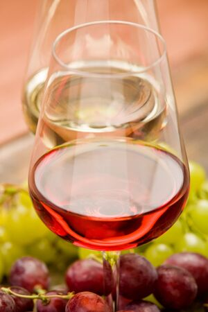 rose and white wine on wooden table with red and white grapes around photo