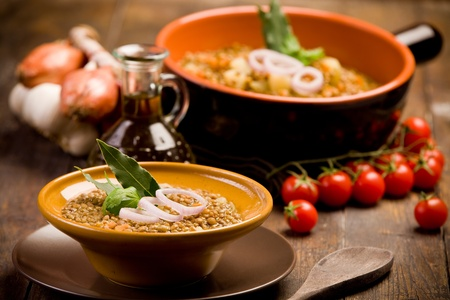 fresh homemade lentils soup with onions and cherry tomatoes on wooden table photo