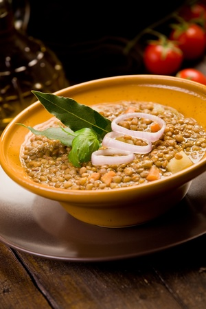 legumes: fresh homemade lentils soup with onions and cherry tomatoes on wooden table