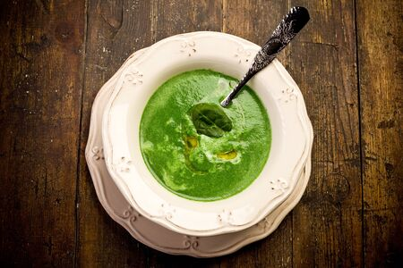 Soft and delicious spinach cream soup on wooden table photo