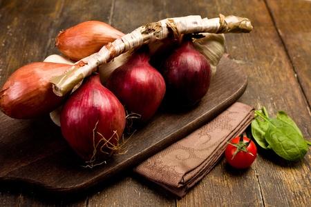 onions: cebollas mezcladas sobre tabla de cortar de madera sobre servilleta marrón