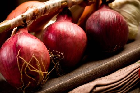 mixed onions on wooden chopping board over brown napkin photo