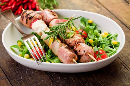 delicious broiled meat skewers on wooden table with salad photo
