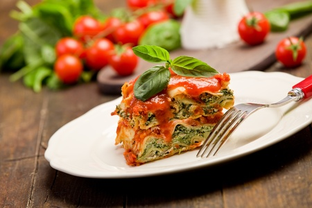 ricotta cheese: delicious homemade lasagne with ricotta cheese and spinach on wooden table