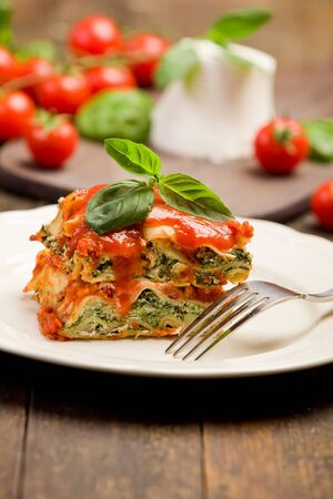 delicious homemade lasagne with ricotta cheese and spinach on wooden table