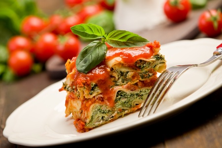delicious homemade lasagne with ricotta cheese and spinach on wooden table photo
