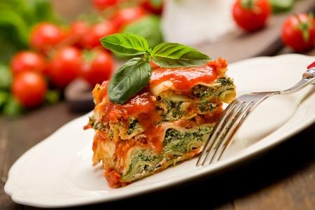 espinacas: lasaña deliciosa hecha en casa con queso ricotta y espinacas en la mesa de madera