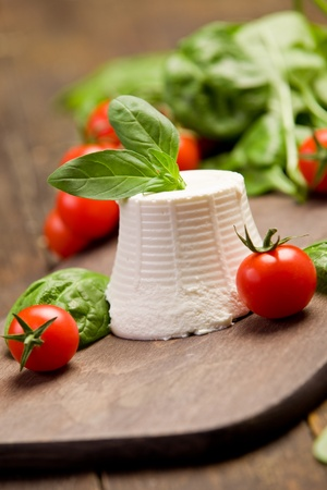 ricotta cheese with basil leaves and cherry tomatoes on wooden table photo