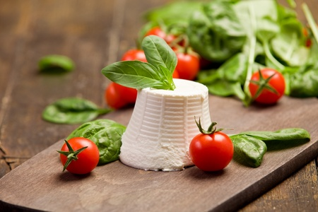 ricotta cheese with basil leaves and cherry tomatoes on wooden table