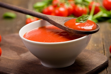 fresh red tomato sauce with basil leaf and wooden spoon photo
