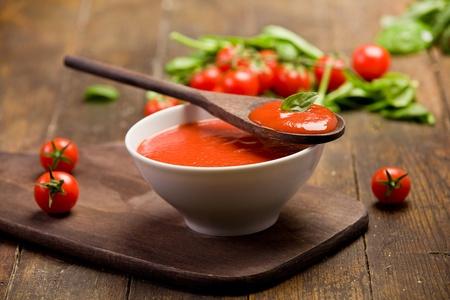 pomidory: świeża czerwona sos pomidorowy z bazylią i łyżka liści drewnianej