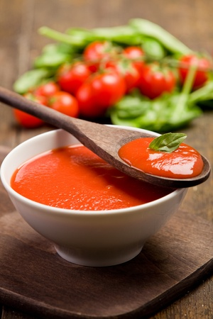 tomato soup: fresh red tomato sauce with basil leaf and wooden spoon Stock Photo