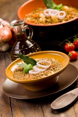 leguminosas: sopa de lentejas fresca hecha en casa con cebolla y tomates cherry en la mesa de madera