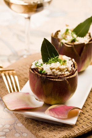 risotto: Stuffed artichokes with risotto on elegant table with golden fork Stock Photo