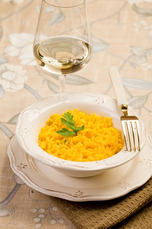 delicious risotto with saffron and golden fork on elegant table photo