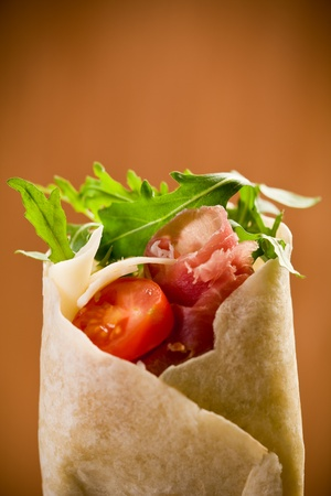 Delicious tortillas stuffed with bacon and colorful arugula salad photo