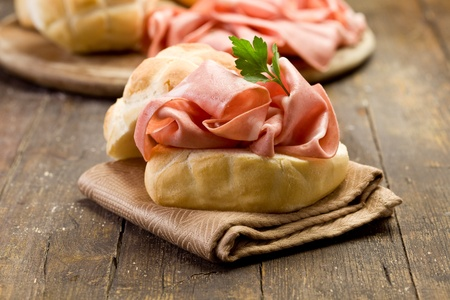 bologna: delicious sandwich on wooden table with mortadella sausage Stock Photo