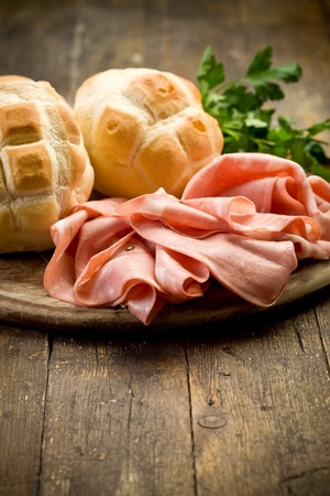 bologna: Sliced soft mortadella sausage on wooden table with bread
