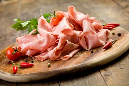 emilia romagna: wooden chopping board with sliced mortadella and red pepper