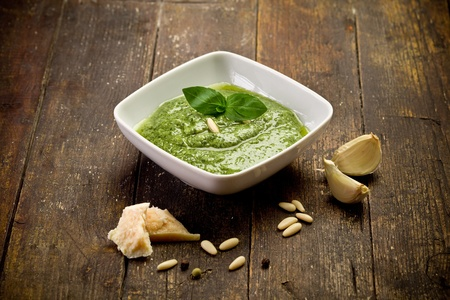 fresh pesto sauce inside a bowl on wooden table