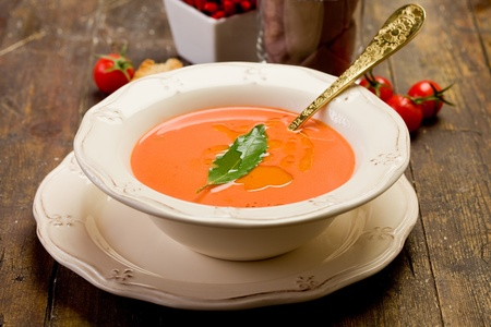 fresh homemade tomato soup with bay leaf on wooden table Stock Photo - 12322951