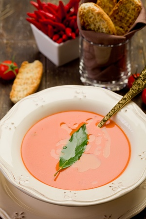 bay leaf: fresh homemade tomato soup with bay leaf on wooden table
