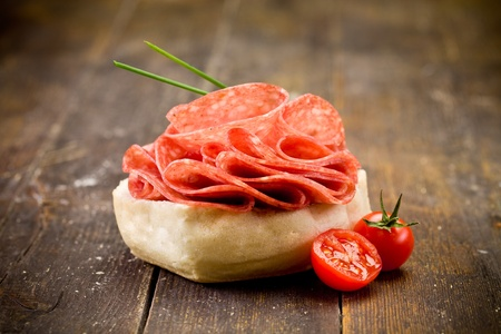 delicious salami sandwich on wooden table photo